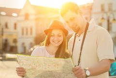Stock Photo of Touristic couple looking at map on the city street under sunligh