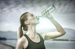 Beautiful female after running, drink water under sky Stock Photos