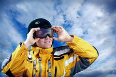 Portrait of man wearing a helmet and glasses on the background of sky with cl - stock photo