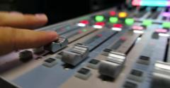 A mans hands pulling up the knobs of an audio mixer in a studio Stock Footage