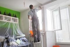 Plasterer renovating indoor walls and ceilings. - stock photo