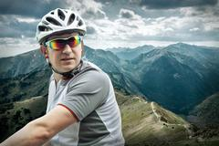 Stock Photo of Men with bicycle aroun mountains beautiful view.