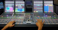 A mans hands pulling the knobs of an audio mixer up and down Stock Footage