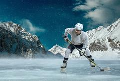 Stock Photo of Ice hockey player in action outdoor around mountains