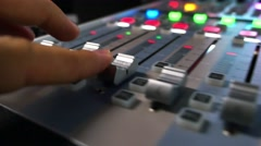 A moving shot of an audio mixer and a man pulling up the knobs on it Stock Footage