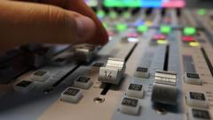 A person pulling up the knobs of an audio mixer in a studio Stock Footage