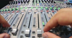 A man working on an audio mixer in a studio, he is pulling the knobs up and down Stock Footage