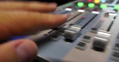 Audio mixer knobs being pulled up quickly by a person working in a studio Stock Footage
