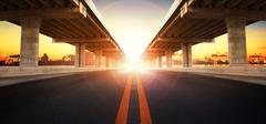 Sun rising behind perspective on bridge ram construction and asphalt raod per Kuvituskuvat