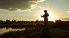 Fisherman fly fishing in lake Stock Footage