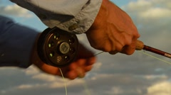 Flyfisher adjusting the string of fishing rod - stock footage