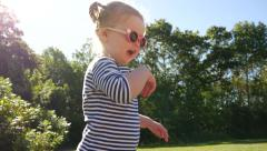 Young girl jumping outside then walks away, slow motion, medium shot Stock Footage