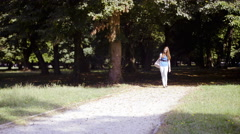 Young woman walking in park with carrying bag and cat 4K  Stock Footage