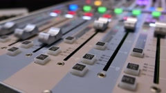Low angle footage of an audio mixer and the knobs being pulled up and down - stock footage
