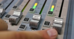 Close up shot of a person adjusting the volume on an audio mixer Stock Footage