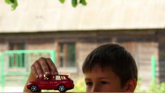 Boy playing with a toy car, a boy dreams of a car, Land Cruiser Stock Footage