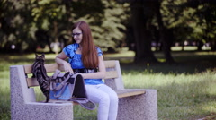 Attractive woman caresses cat on wooden bench in park 4K  Stock Footage