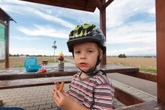 Little boy cyclist snack. Stock Photos