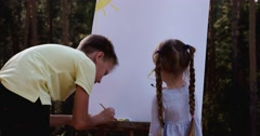Little girl painting color on easel Stock Footage