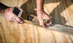 Carpenter's hands working with the old wooden jointer - stock photo