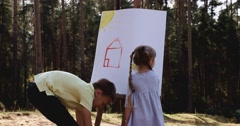 Cute adorable young kids with crayons at an outside playschool Stock Footage