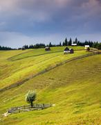 Country scene with wooden huts on the hill and sky rain - stock photo