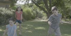 Three kids running together in slow motion - stock footage