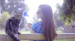 Woman and cat rest on bench in park 4K  Stock Footage
