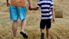 Father and son are going on a field near the haystacks mown field Stock Footage