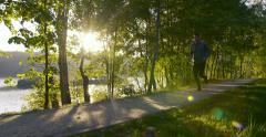 Man running in park during sun rise – slow motion Stock Footage