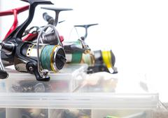 fishing reels on storage boxes with baits - stock photo