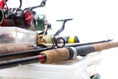 fishing reels and rods on storage boxes - stock photo