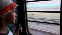 Boy riding on a train and looking out the window, vestibule of the train Stock Footage