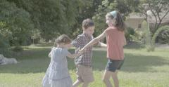 Two girls and a boy playing and dancing outside Stock Footage