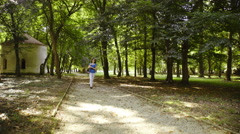 Female person walking on gravel path in park 4K  Stock Footage