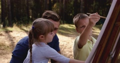 Father painting with his children in a park Stock Footage