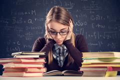 Student with desperate expression looking at her books Stock Photos