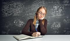 Thinking  student sitting at a desk Stock Photos