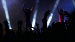 Stock Video Footage of Dancing fan spectator silhouettes on concert lumiere cheerfully jumping hands up