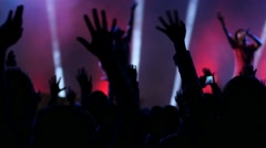Dancing fan spectator silhouettes on concert lumiere cheerfully jumping hands up Stock Footage