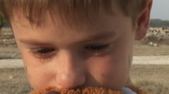Dirty little orphan boy close-up crying and petting a stuffed toy on the Stock Footage
