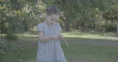 Little girl wearing a dress playing with a wooden stick Stock Footage