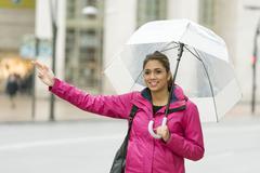 Beautiful latin woman with umbrella hitchhiking in the street. Stock Photos