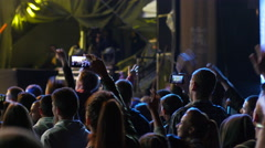 Jumping fan spectator silhouettes on concert lumiere cheerfully dancing hands up Stock Footage