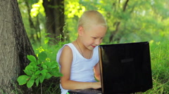 5 years old boy in white clothes sitting in the park under a tree and talking to Stock Footage