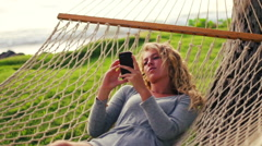 Young Woman Laughing Using Mobile Smart Phone while Relaxing in a Hammock by  Stock Footage