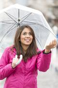 Smiling young woman with umbrella checking for rain. - stock photo