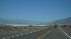 Motorcycles to Lake Owens, HIGHWAY, driving by desert mountains - stock footage