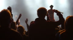 Fan spectator silhouettes on concert lumiere cheerfully swaying hands in air Stock Footage