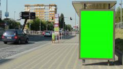 Green screen billboard on the bus stop in the city - cars pass around Stock Footage
